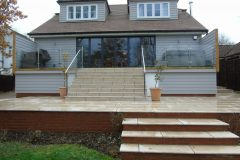 Cladded bespoke terrace with brick dwarf wall. Oak trim with infinity glass & natural stone steps & patio area